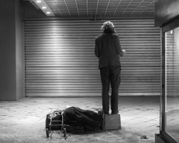 Mann steht auf einer Kiste auf dem Bürgersteig und dirigiert ein unsichtbares Orchester. An Stelle des Orchesters ist ein Roolladen (Rolltor) zu sehen.